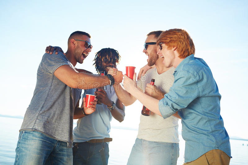Guys on the beach. Happy buddies with drinks arm-wrestling on beach stock images