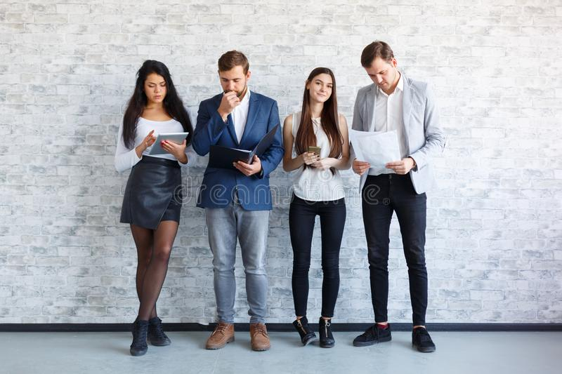 The guys and a girl are standing and holding document, folder, a tablet and phones. Indoors. stock image
