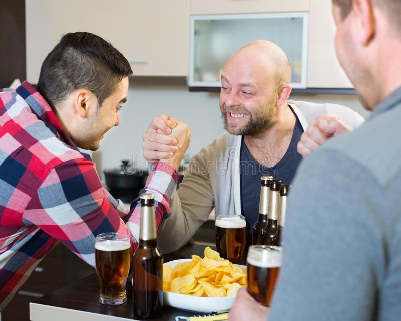 Guys having arm wrestling competition. Adult guys having arm wrestling competition and laughing at house party stock photo