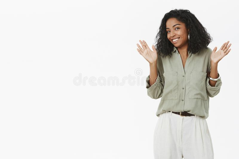 Guys I am out of this. Portrait of uninvolved charismatic young dark-skinned employer in blouse raising palms near royalty free stock image