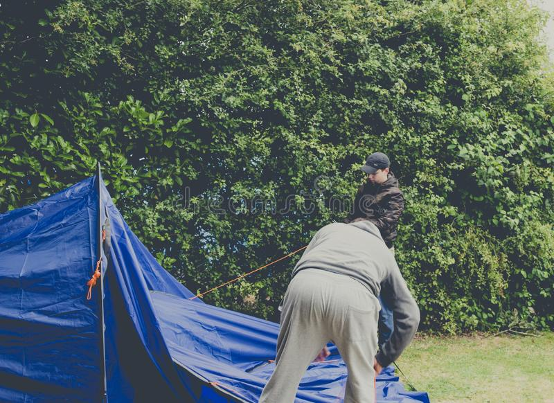 Guys pitching tent camping stock photo
