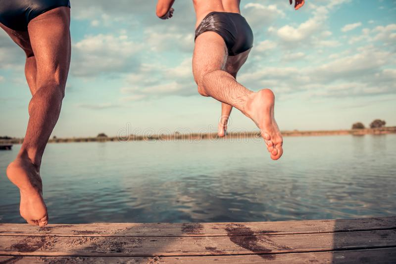 Guys on the sea. Cropped image of handsome guys jumping from pier into the lake, beautiful view royalty free stock images