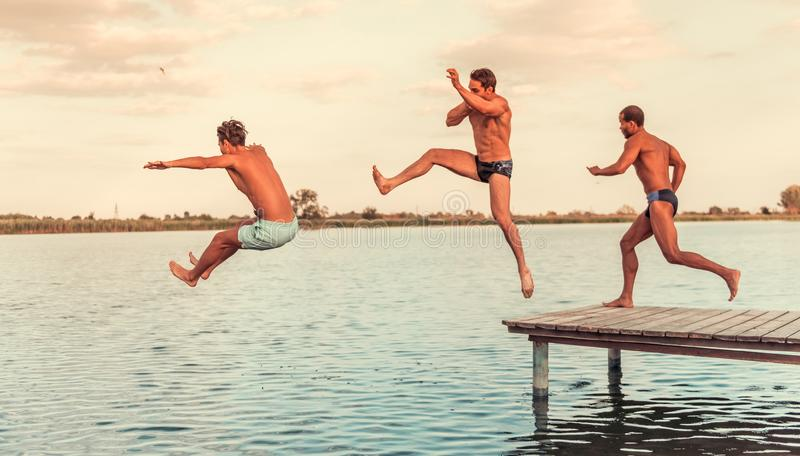 Guys on the sea. Handsome guys are jumping from pier into the lake, beautiful view stock images
