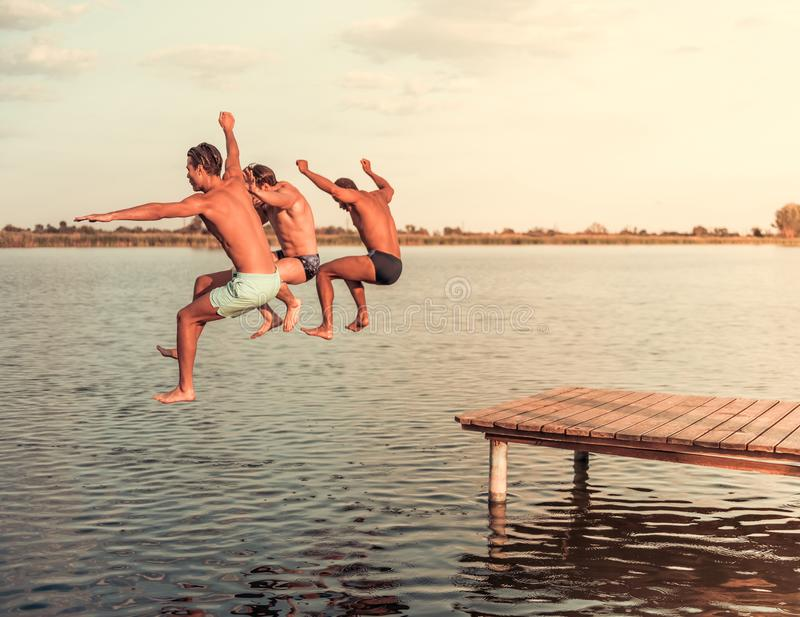Guys on the sea. Handsome guys are jumping from pier into the lake, beautiful view royalty free stock photo