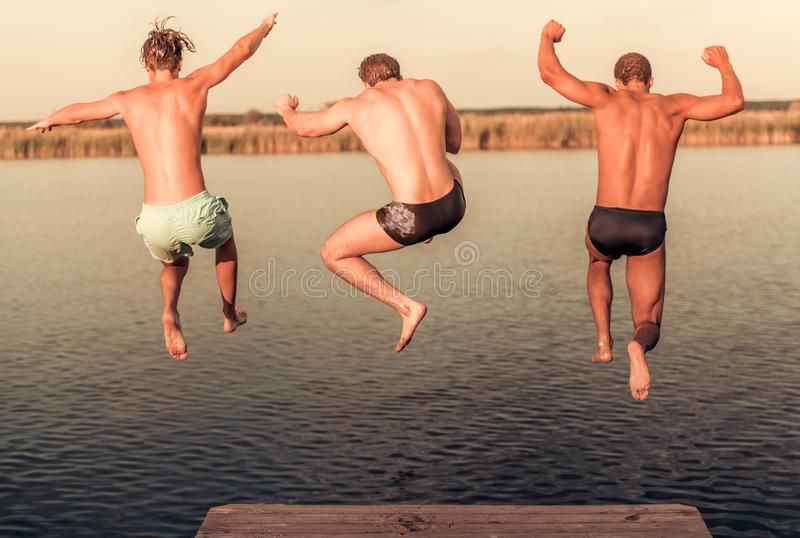 Guys on the sea. Handsome guys are jumping from pier into the lake, beautiful view stock photo