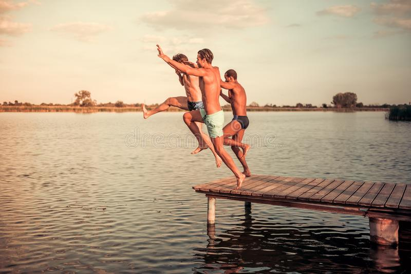 Guys on the sea. Handsome guys are jumping from pier into the lake, beautiful view royalty free stock images