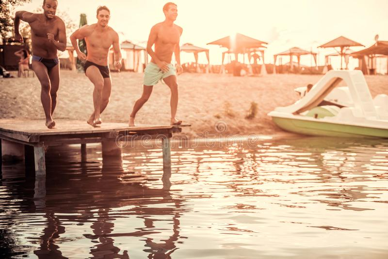 Guys on the sea. Handsome guys are jumping from pier into the sea, sun is going down stock images