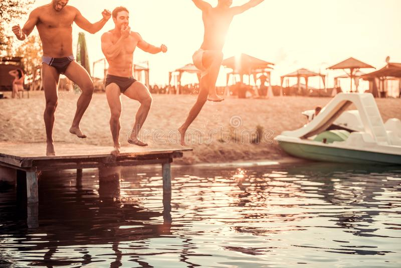 Guys on the sea. Handsome guys are jumping from pier into the sea, sun is going down stock photos