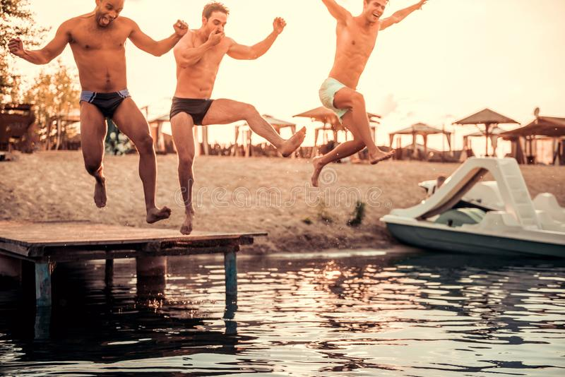 Guys on the sea. Handsome guys are jumping from pier into the sea, sun is going down royalty free stock image