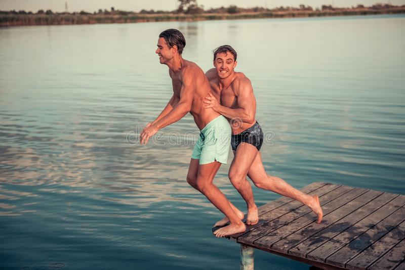 Guys on the sea. Handsome guys are pushing each other from pier into the lake, beautiful view royalty free stock images