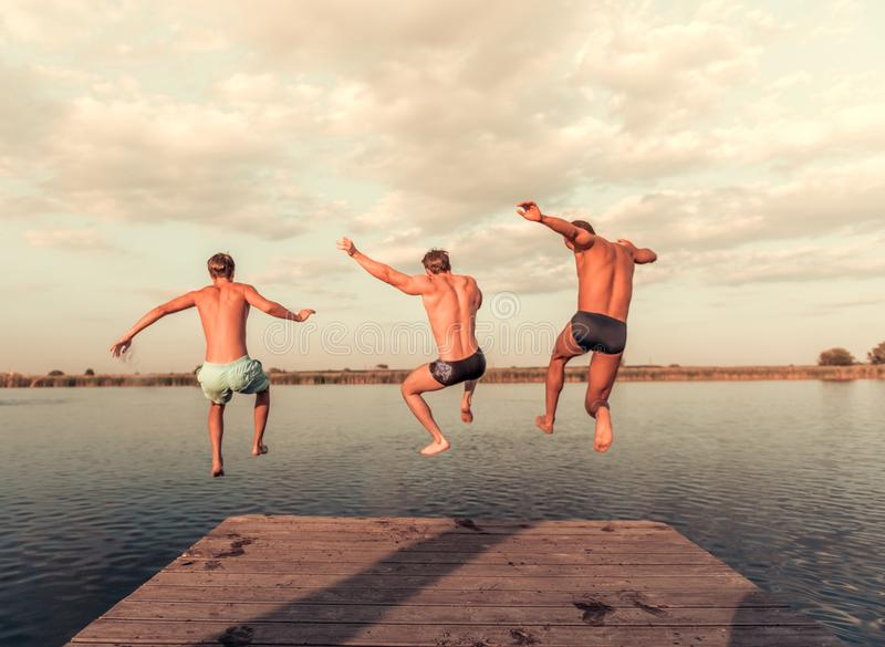 Guys on the sea. Handsome guys are jumping from pier into the lake, beautiful view stock image