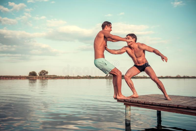 Guys on the sea. Handsome guys are pushing each other from pier into the lake, beautiful view stock image