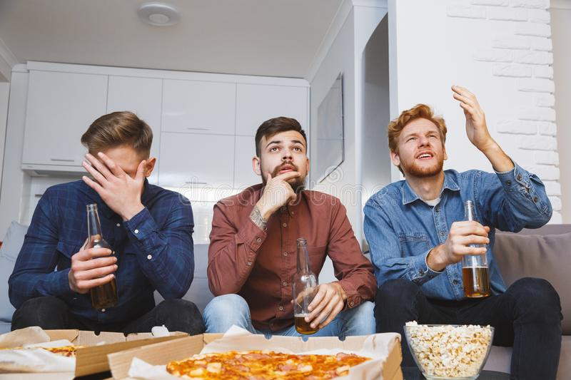 Men watching sport on tv together at home loss stock photo