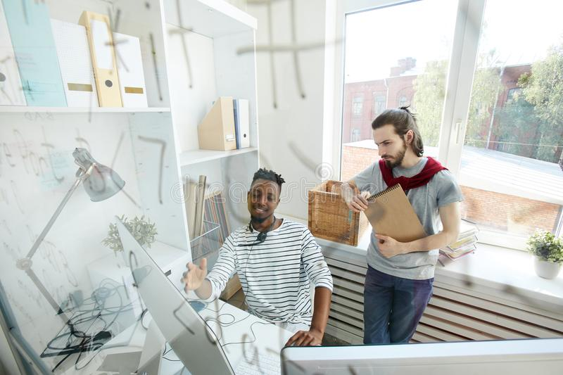 It-guys at work. Two hipster guys in casualwear looking at computer screen and discussing data or software language royalty free stock image