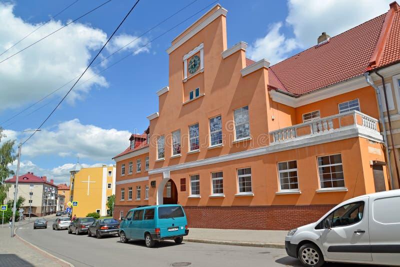 GVARDEYSK, RUSIA Vista de la calle de Telman y del edificio de la escuela del ` s de los niños del ayuntamiento anterior de los a foto de archivo