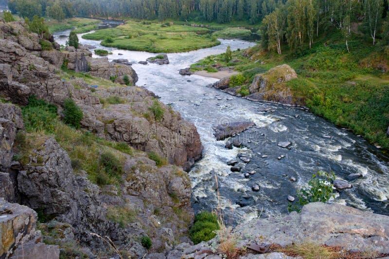 Gwałtowni na rzece wartko biega wśród kamieni i drewien fotografia stock