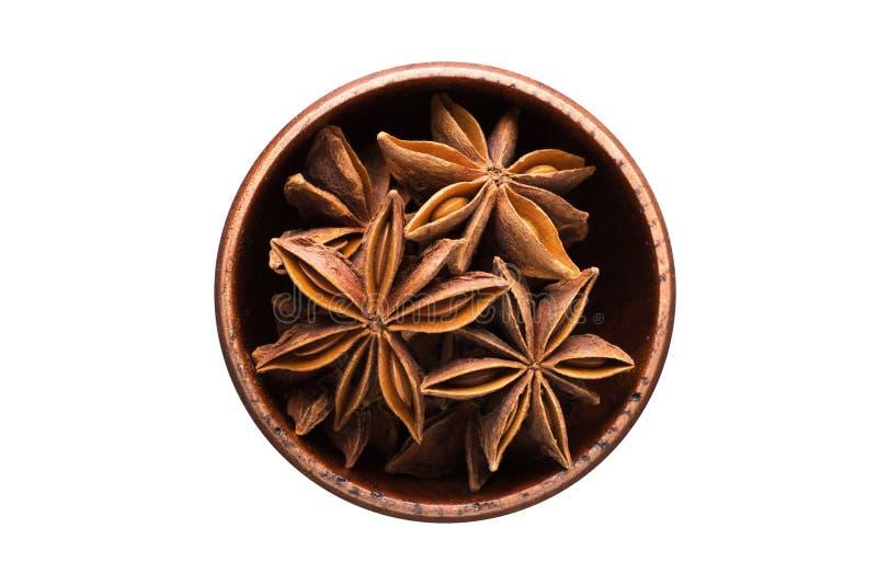 Gwiazdowego anyżu pikantność w drewnianym pucharze, odosobnionym na białym tle S zdjęcia royalty free