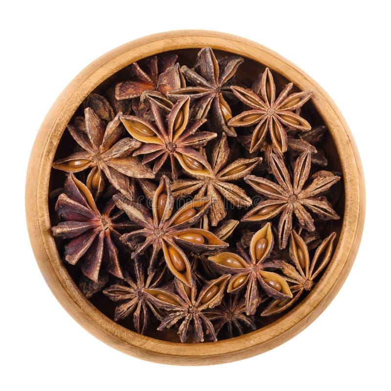 Gwiazdowego anyżu ziarna w drewnianym pucharze nad bielem fotografia royalty free