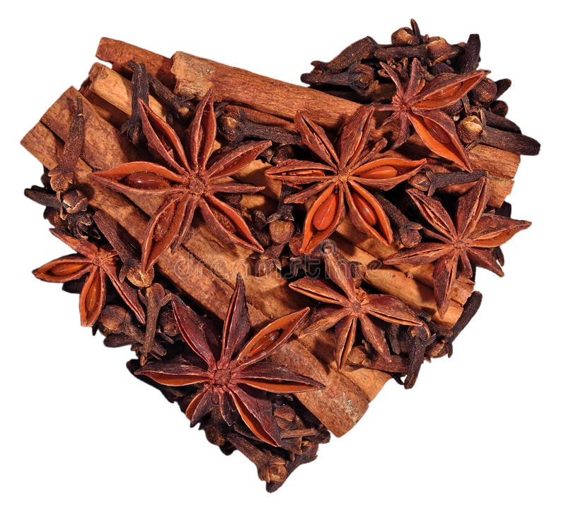 Gwiazdowy anyż, cynamonowi kije i cloves w postaci serca na a, fotografia stock