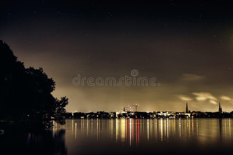 Gwiazdy czernią Alster Niemcy miasta Jeziornych drzewnych Hamburskich sławnych bożych narodzeń żeglowania panoramy nieba nocy chm zdjęcie stock