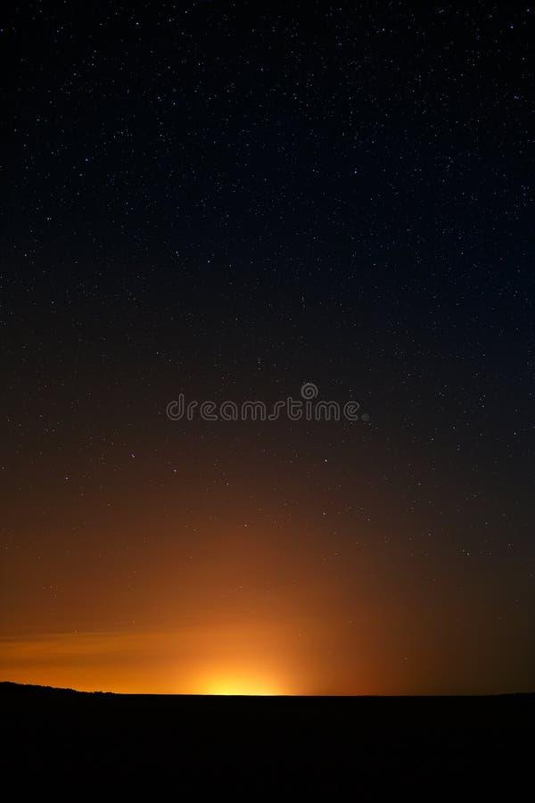 gwiazdy w nocnym niebie przeciw tłu miasta skyl obraz royalty free