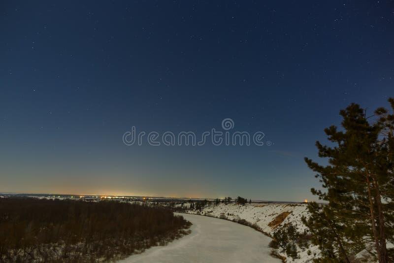 Gwiazdy w nocnym niebie Zima krajobraz z zamarzniętą rzeką fotografującą pod księżyc w pełni obrazy royalty free