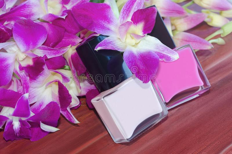 Gwoździa połysku butelki i różowi storczykowi kwiaty zdjęcia stock