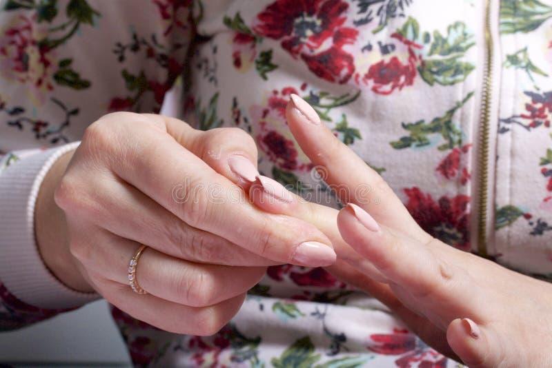 Gwoździa narzut z lakierem Kobieta stosuje gwoździa połysk na ona gwoździe zdjęcia stock