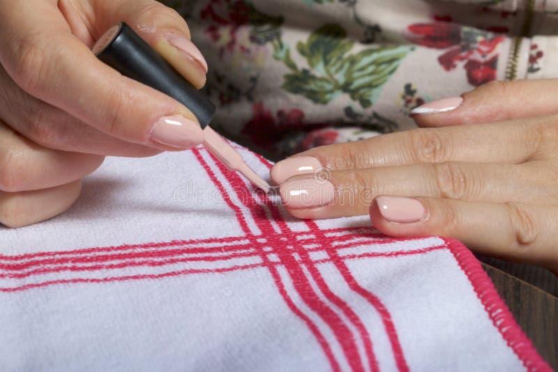 Gwoździa narzut z lakierem Kobieta stosuje gwoździa połysk na ona gwoździe obrazy stock