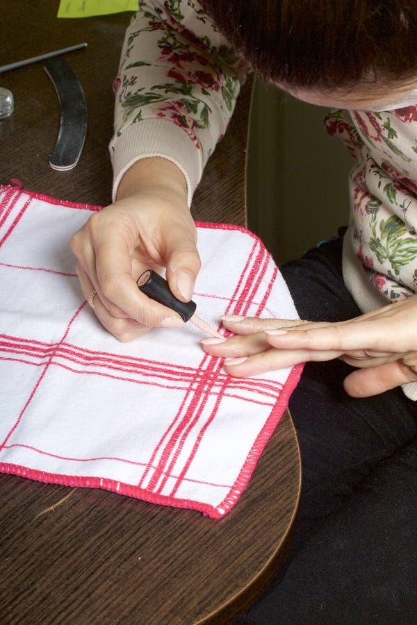 Gwoździa narzut z lakierem Kobieta stosuje gwoździa połysk na ona gwoździe obraz stock