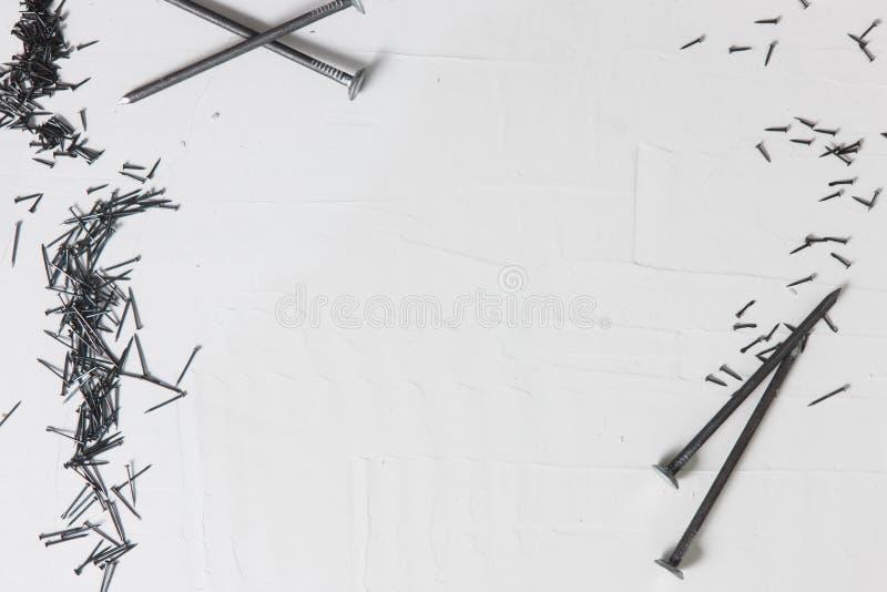 Gwoździe na bielu, budowy tło, rama obrazy stock