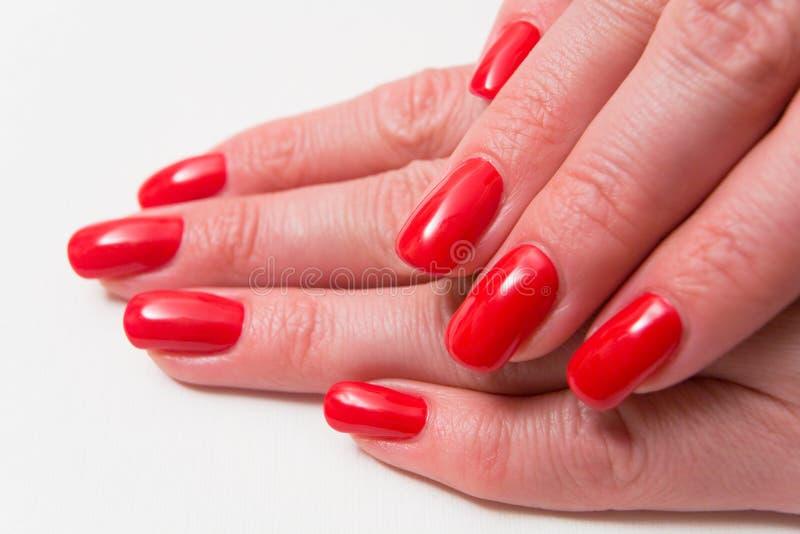 Gwoździe piękni żeńscy palce zakrywają z czerwień lakierem obraz stock