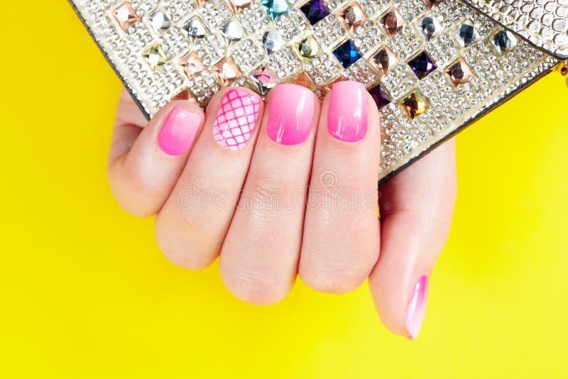 Gwoździe z manicure'em zakrywającym z różowym gwoździa połyskiem, żółty tło zdjęcie royalty free