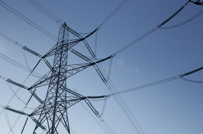 Power supply pylons against a blue sky. Elasticity pylons against a clear blue sky on a cold winters day in Scotland stock images