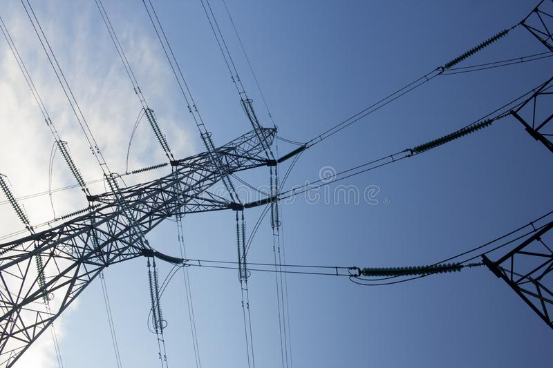 Power supply pylons against a blue sky. Elasticity pylons against a clear blue sky on a cold winters day in Scotland royalty free stock photo