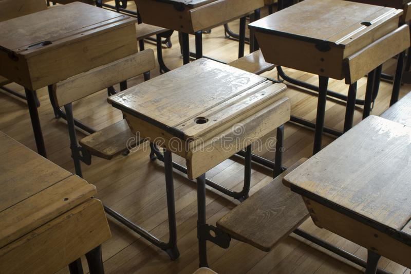 A old style school desks. Rows of old fashioned school desks in a classroom in day light royalty free stock photo
