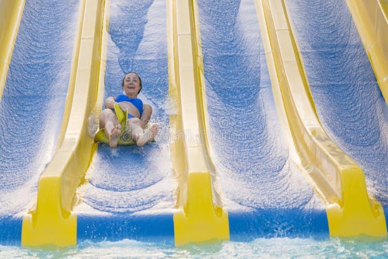 Gyckel i dennätta flickan i bikini kommer ner vattenbanan in till simbassängen Härlig flicka som rider en vattenglidbana lycklig  arkivbilder