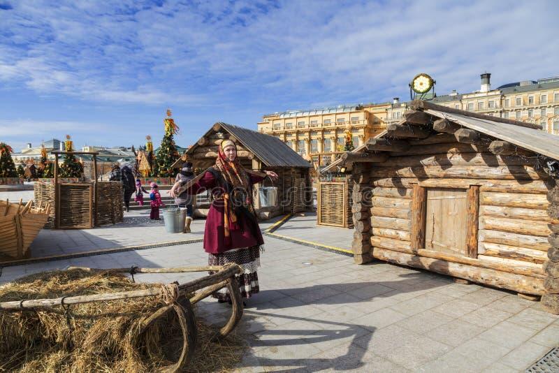 Gyckel på berömmen av Maslenitsa på den Manege fyrkanten i Moskva En kvinna i landskapet av en rysk by bär vippa a arkivfoton