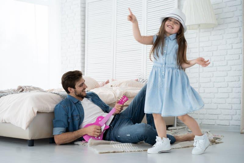 gyckel som tillsammans har Barnet avlar att spela gitarren för hans lilla dotter och att le, medan spendera fri tid hemma royaltyfria foton