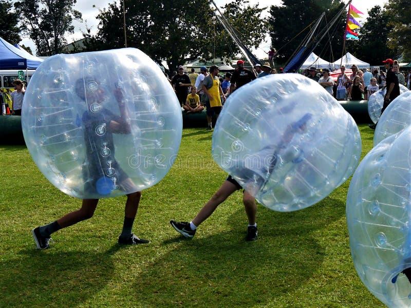 Gyckel: två pojkar som spelar bulabollar som zorbing royaltyfria bilder