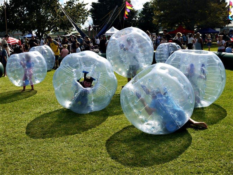 Gyckel: ungar som spelar bulabollar som zorbing arkivbild