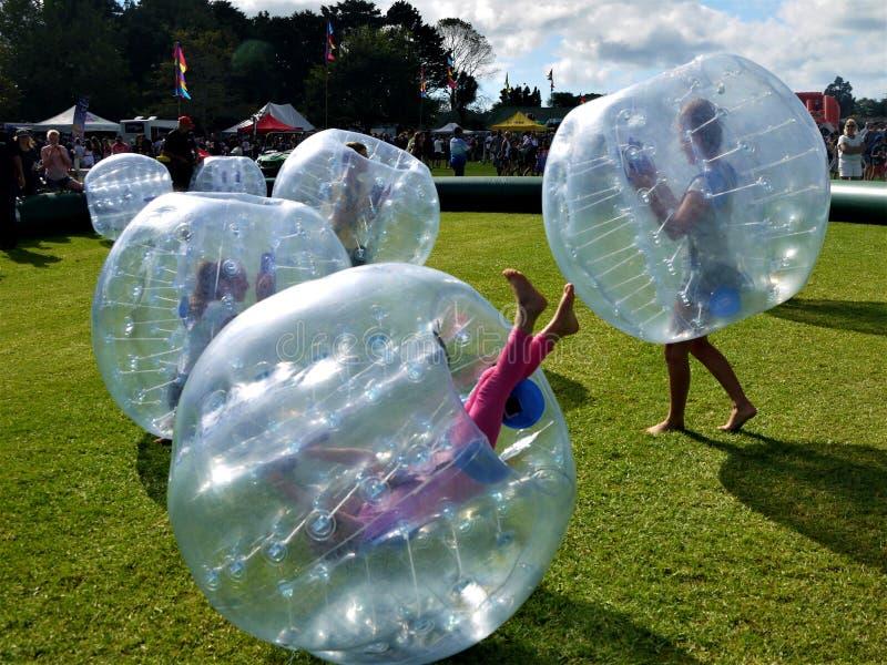 Gyckel: ungar som studsar i bula, klumpa ihop sig zorbing royaltyfria foton
