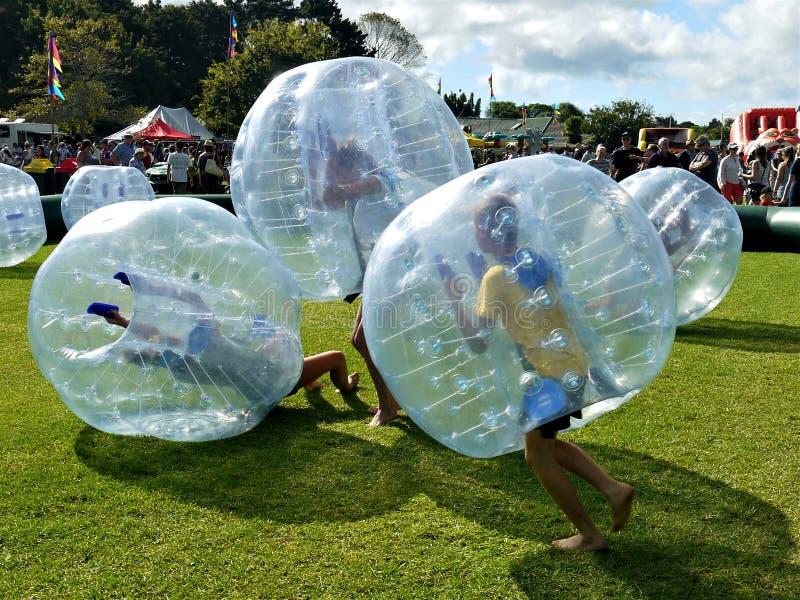 Gyckel: ungegrupp som spelar bulabollar som zorbing royaltyfria bilder