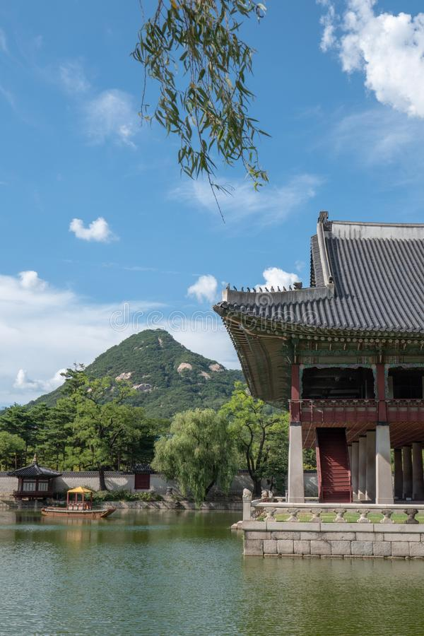 Gyeongbokgung Palace with pond and boat. Mountain at the back and blue sky royalty free stock photos