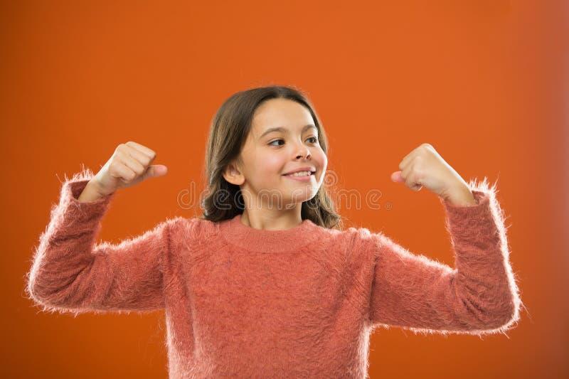 Gyllene regler för att lyfta mentalt starka ungar För flickashow för barn gör en gest den gulliga bicepens av makt och styrka Kän royaltyfri bild