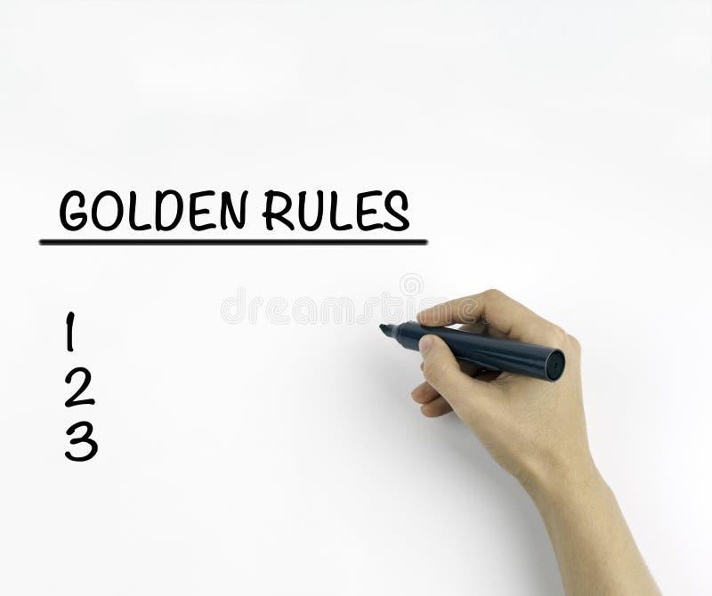 Gyllene regler på en vit bakgrund royaltyfria bilder