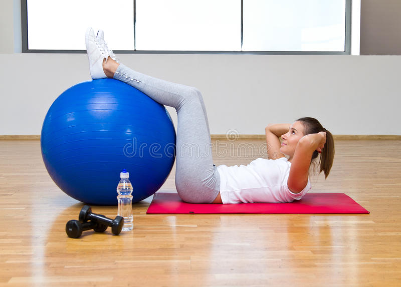 At the gym. Beautiful woman exercising at the gym