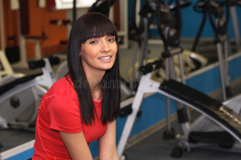 In a gym. A young smiling woman in a gym royalty free stock images