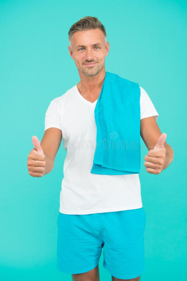 Gym aesthetics. Man well groomed athlete with towel on blue background. Mature but still in good shape. Exercising in royalty free stock photo
