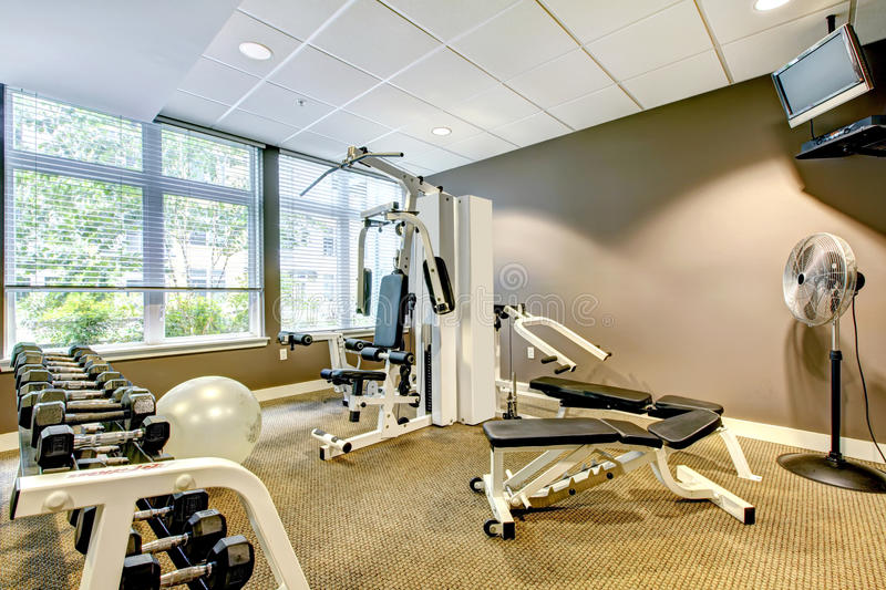 Gym in apartment building with brown wall and TV. Small Gym in apartment building with brown wall and TV royalty free stock photo